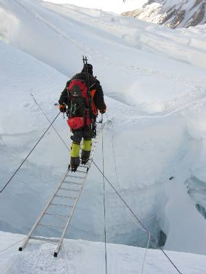 Fiona carefully negotiates a two ladder crossing near the top of the icefall. Photo Paul Adler.