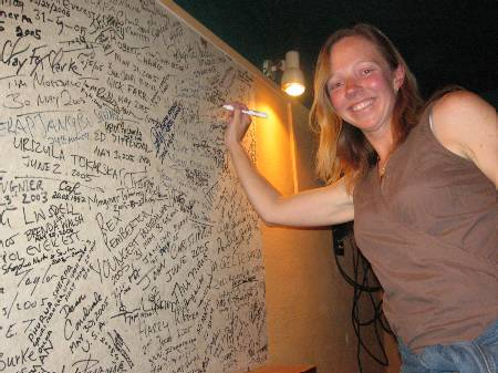 Fiona signs her name on the Rumdoodle signature board for Everest summiteers. Photo Paul Adler.