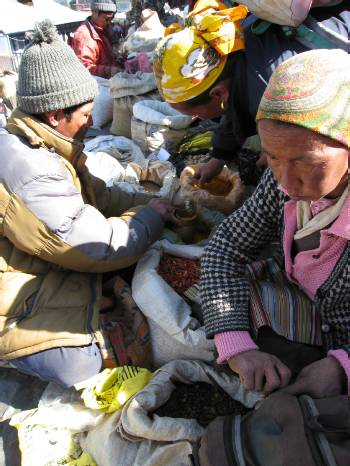 Namche market trader selling spices and beans.