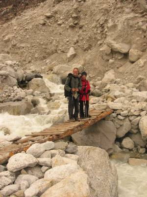 Paul and Mary on a log bridge over the river that comes out of the Khumbu Glacier near Dugla. Photo Fiona Adler.