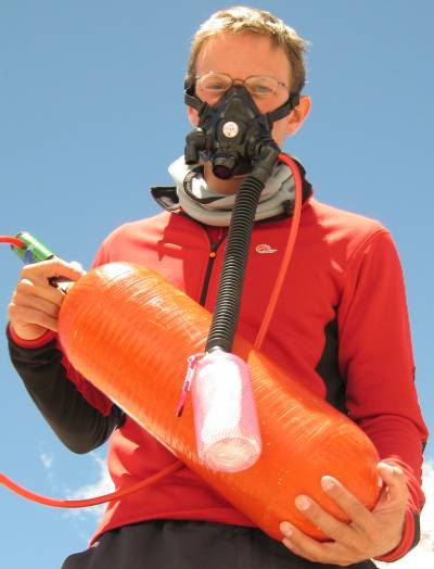 Paul wearing the new Top Out mask and holding an IMG oxygen bottle. You can see the green regulator at the top of the bottle which adjusts the flow rate. Photo Fiona Adler